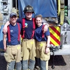 Picture of three firefighters posing behind a fire truck.