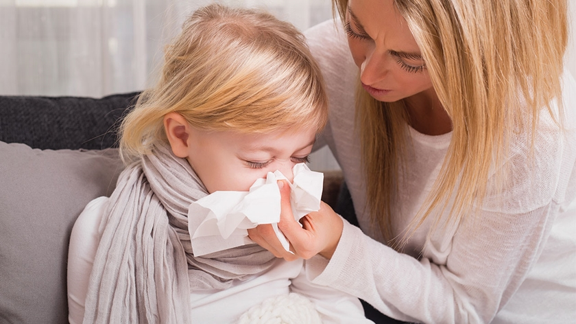 A woman with long blonde hair and wearing a white shirt holds a tissue up to a young girl's nose while she blows her nose.