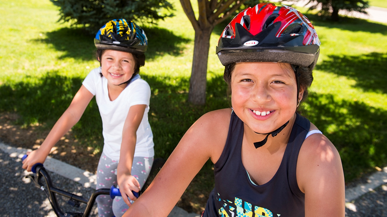 Girls ride bikes together.
