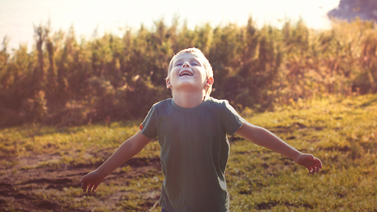 A school-age boy wearing a short sleeve gray shirt stands in a field with tall grasses behind him while the sun shines down. He is looking up smiling with his eyes closed and his arms out to the side.