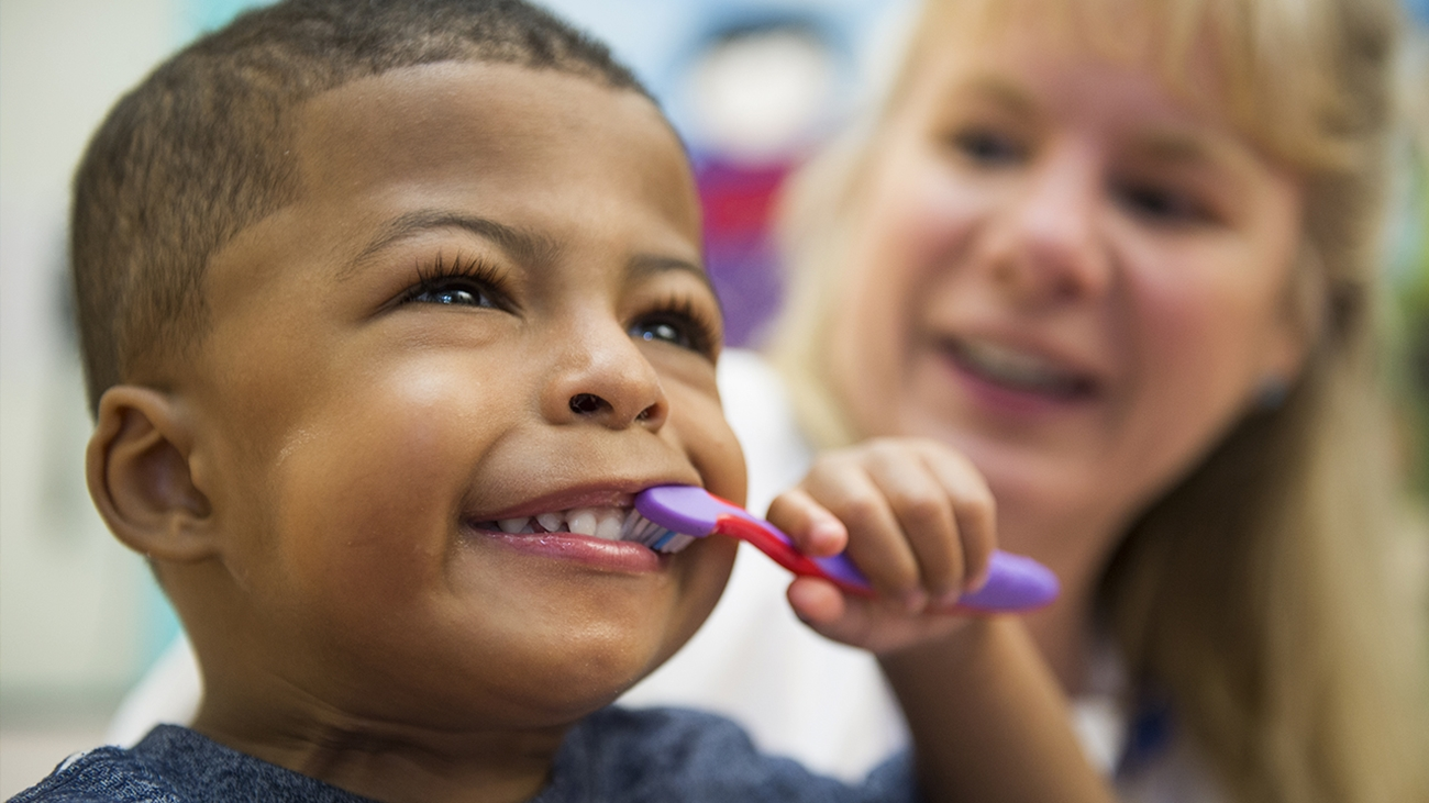 A young boy wearing a blue shirt smiles and brushes his teeth with a purple and pink toothbrush while a doctor with long blonde hair watches in the background.