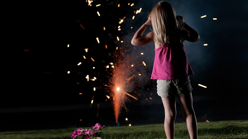 A young girl watches fireworks shoot up from the ground.