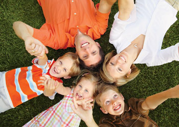A family consisting of a mom, dad, two boys and a girl lie on their backs in the healthy green grass with their heads together, forming a circle. In clockwise order: The dad is wearing an orange button down shirt. The mom is wearing a white blouse. The boy next to her is wearing a brown polo. The girl is wearing a red, yellow, and orange plaid dress. And the boy next to her is wearing an orange shirt with blue and white stripes.