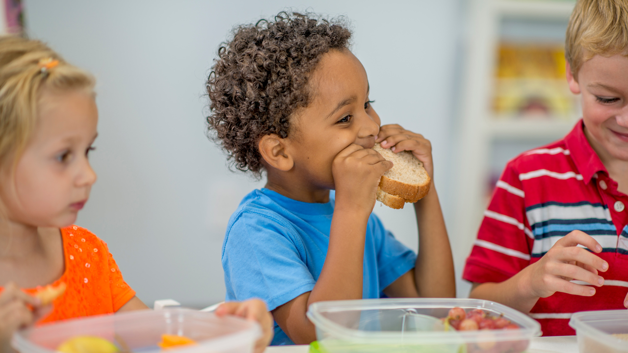 A child eats a peanut butter sandwich at a school lunch table.