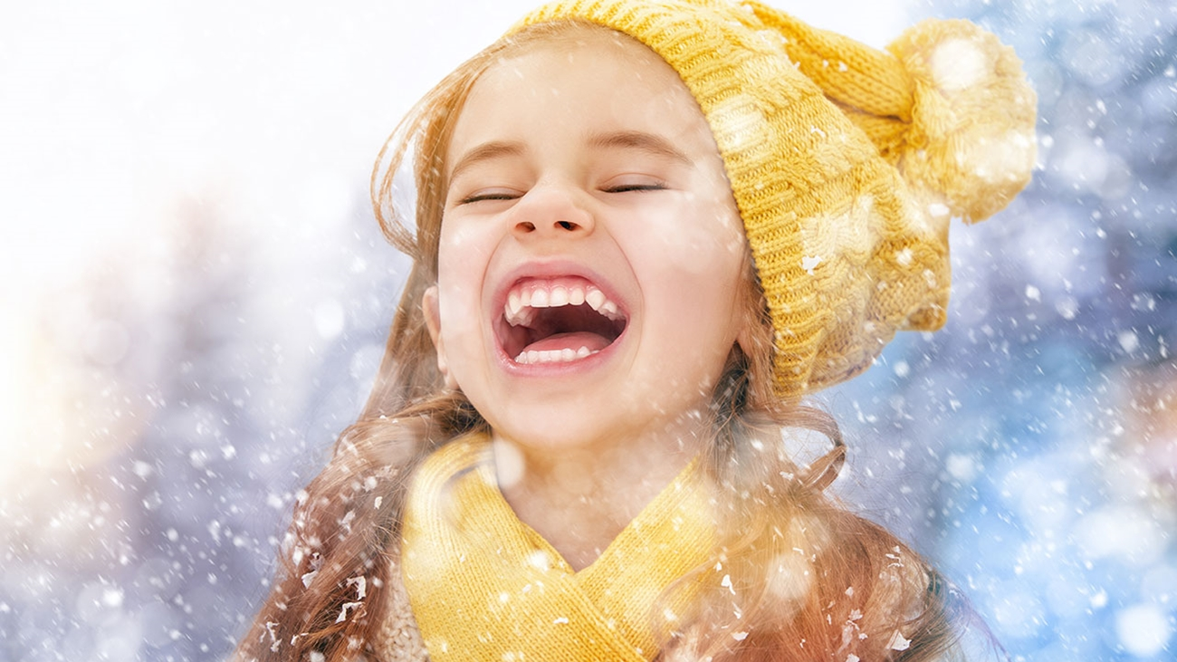 A close-up of a girl with long brown hair, wearing a yellow knit hat and a yellow scarf, laughing as snow falls down around her.