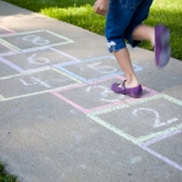A child builds healthy bones by playing hopscotch on a sidewalk.