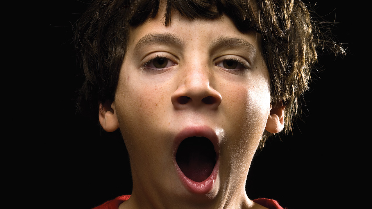 A close-up of a boy with thick brown hair yawning