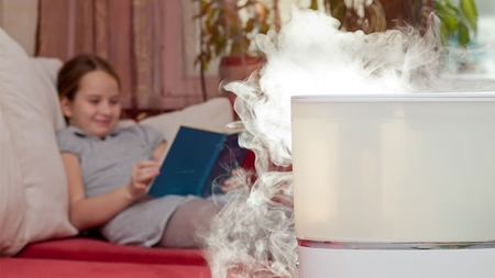 A white humidifier has a smokey vapor coming out of it while a young girl reads a blue book on a red bed with white pillows in the background.