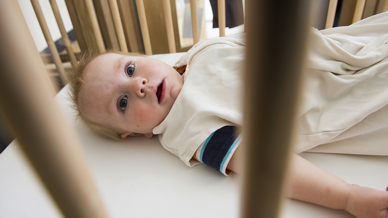 A baby lying in a crib wearing a beige sleep sack over blue striped pajamas.