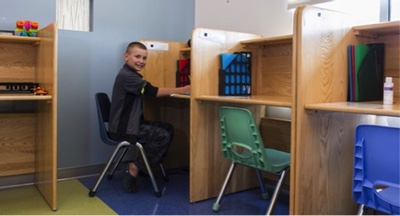A boy sits in a chair at a desk partition.