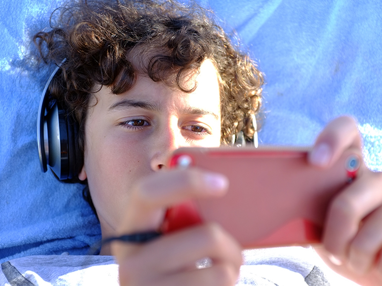 A teenage boy with brown, curly hair lies down watching his phone with big headphones on.