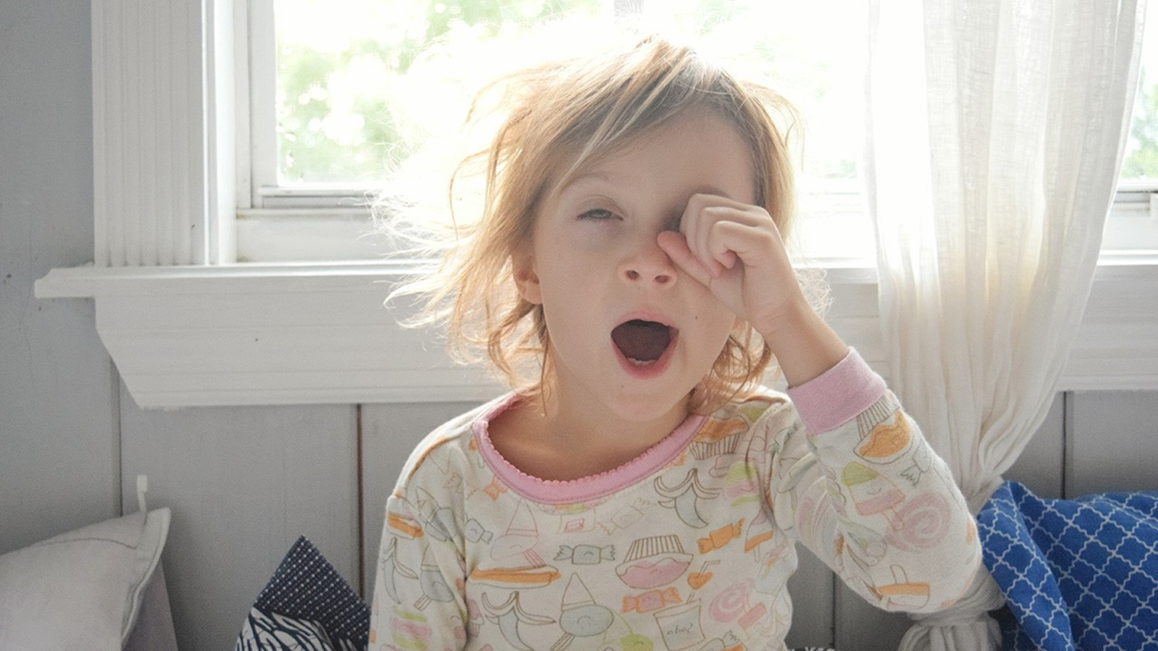 A young girl in pajamas yawning and rubbing her eye.
