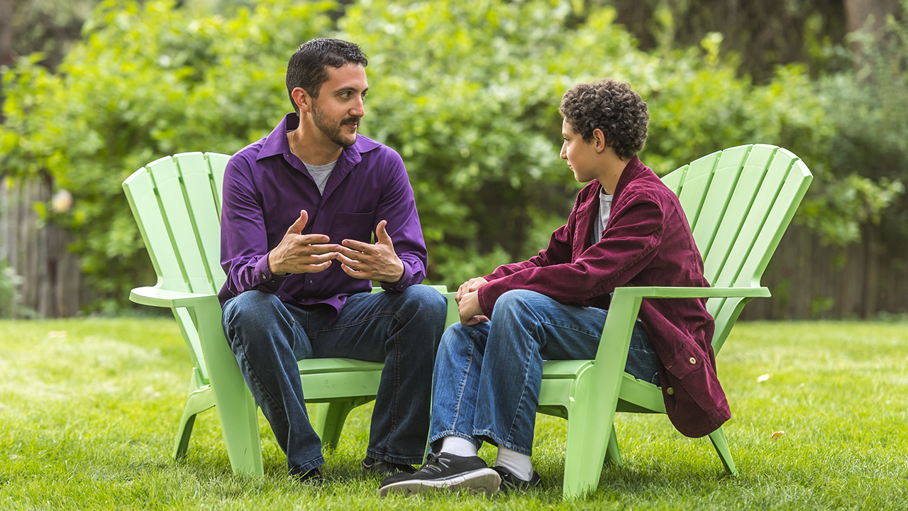 A father talks to his son while sitting outdoors.