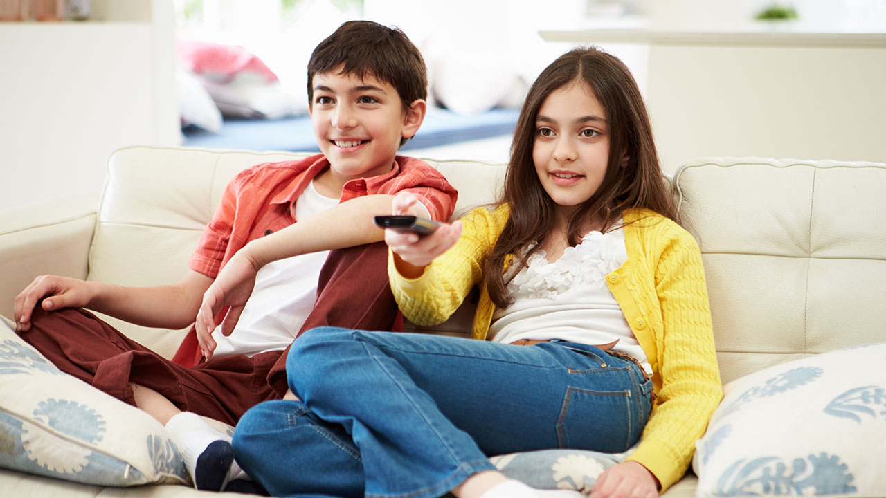 A boy and girl sit on a couch watching TV.