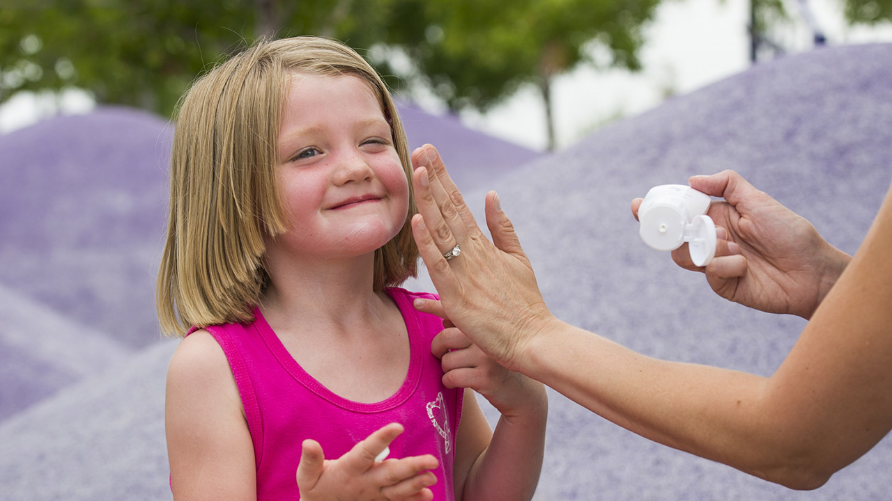 A woman puts sunscreen on a young girl with light brown hair and wearing a pink tank top at a park.