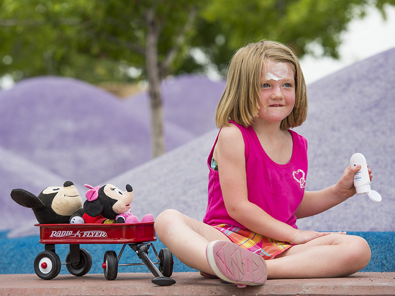 A girl wearing a pink tank top and matching plaid shorts applies sunscreen while sitting on the concrete next to a little red wagon with mickey and minnie mouse dolls in it.