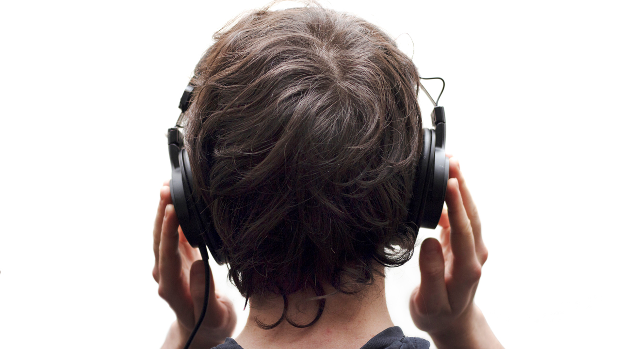 The back of a teen's head with headphones on