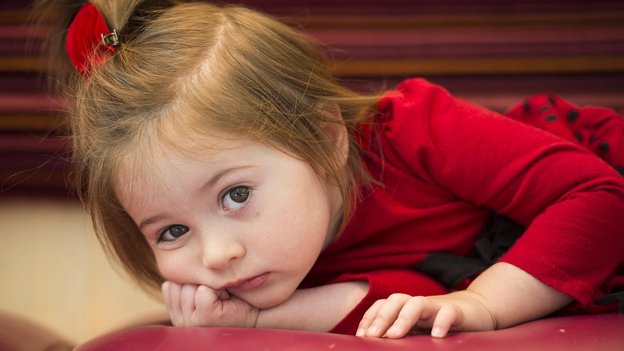 A closeup of a toddler girl with brown hair pulled back in a red bow, wearing a red dress and lying on the ground.