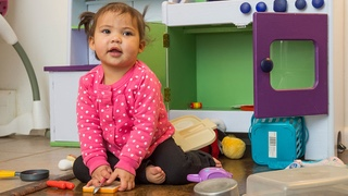 A toddler wearing a pink sweater with white dots kneels on the floor playing with toy kitchen pieces in front of an open toy oven.