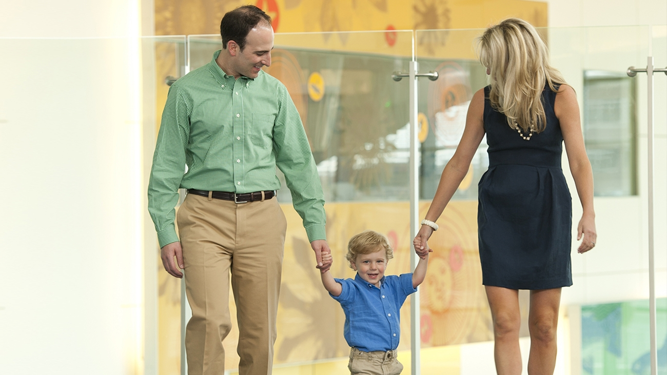 A mom and dad hold a young boy's hands while they walk.