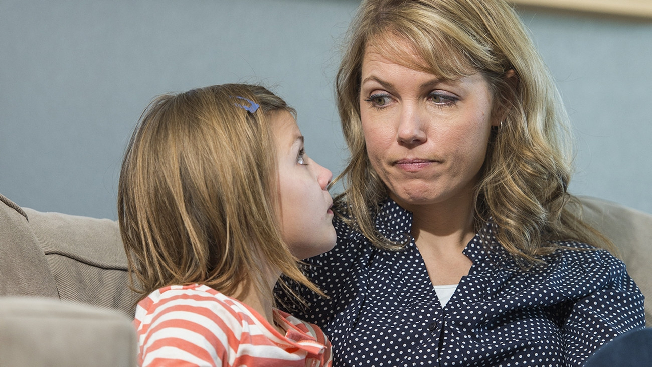 A woman with blonde hair and wearing a blue shirt with small polka-dots gives a disapproving look to a school-age girl wearing an orange and white striped shirt.