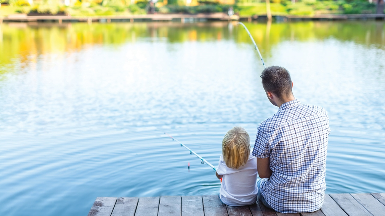 Dad is wearing a blue and brown plaid short-sleeve button-down shirt sitting next to  son, who has long blond hair and is wearing a white t-shirt, on the dock fishing in a lake.