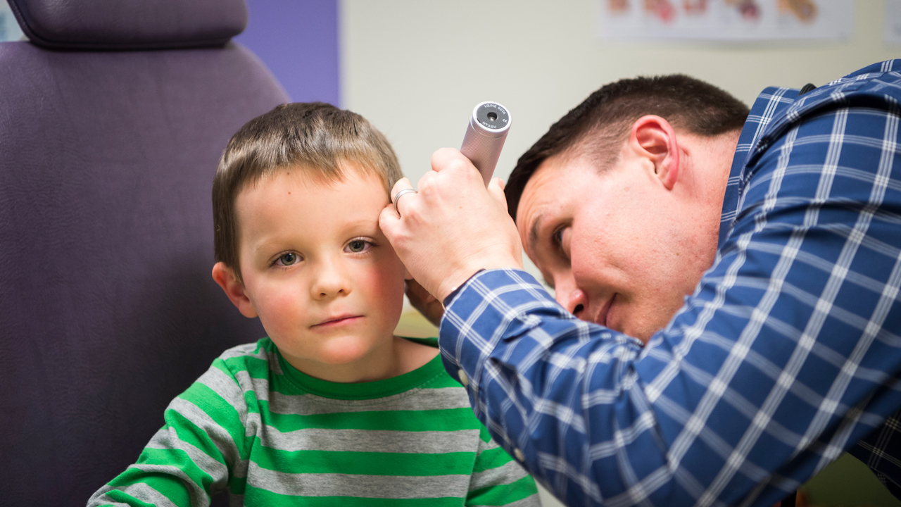 An ENT doctor looks at a kid's ear