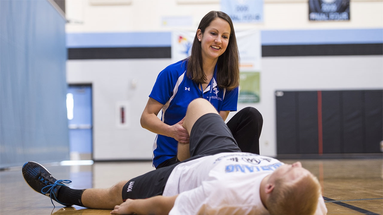 An athletic trainer checks a young male athletes knee after a knee injury.