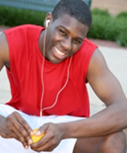A teenage athlete wearing headphones and peeling an orange.