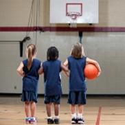 Three girls in navy blue jerseys stand on a basketball court holding a ball and looking at the basket.