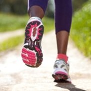 A closeup of a women's feet running on a trail in a park.