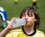 A boy in a yellow jersey drinks from a water bottle at a soccer field.