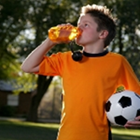 A boy in an orange jersey holding a soccer ball and drinking from a water bottle.