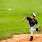 A little league pitcher stands on the mound after throwing the ball toward the plate.