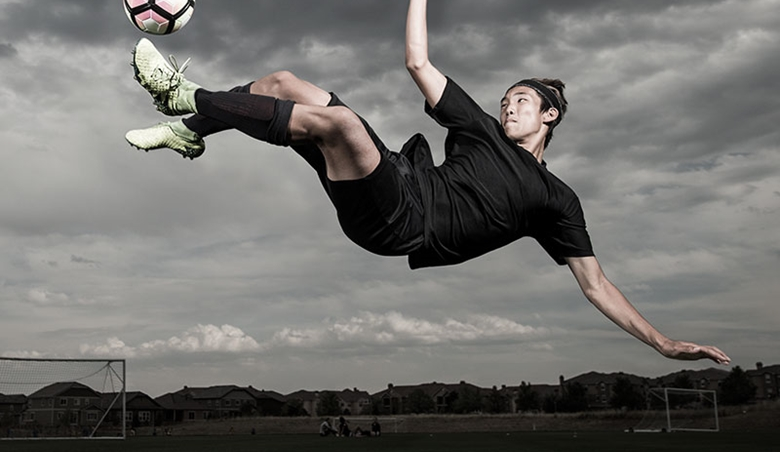 A teenage soccer player kicks the ball sideways in the air.