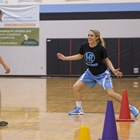 A Sports Medicine Center physical therapist stands in a gym, helping a teenage athlete recover from her sports injury.