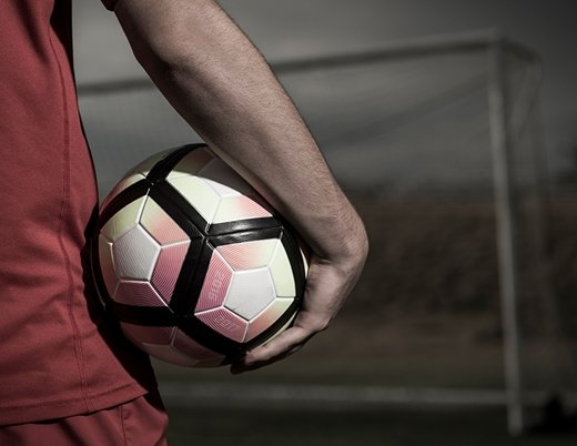 A teenager holds a soccer ball.