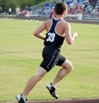 A teenage boy in a black uniform runs on a track.