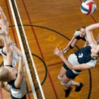 A girl spikes the ball over the net while two girls on the other side try to block it.
