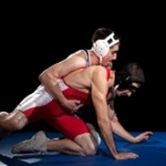 Two teenage boys wrestle on a wrestling mat.
