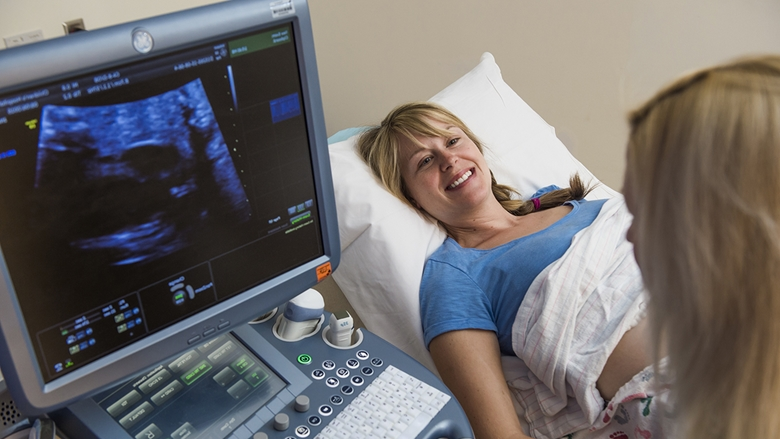 A smiling blond woman in a blue shirt lies on an exam table. Dr. Howley looks at a screen on a computer-like machine showing fetal ultrasound results.