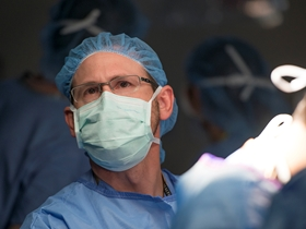 A doctor at the Colorado Fetal Care Center looks up during surgery.