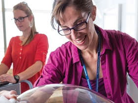 Dr. Kristen Nadeau smiles over a patient. She's wearing glasses, a magenta tank top and matching button down shirt and has her brown hair in a ponytail.