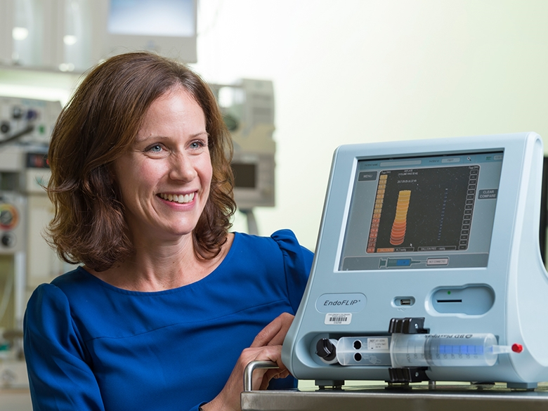 A woman in a blue shirt sits smiling at a EndoFLIP machine.