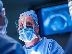 A surgeon operates wearing a clear face shield