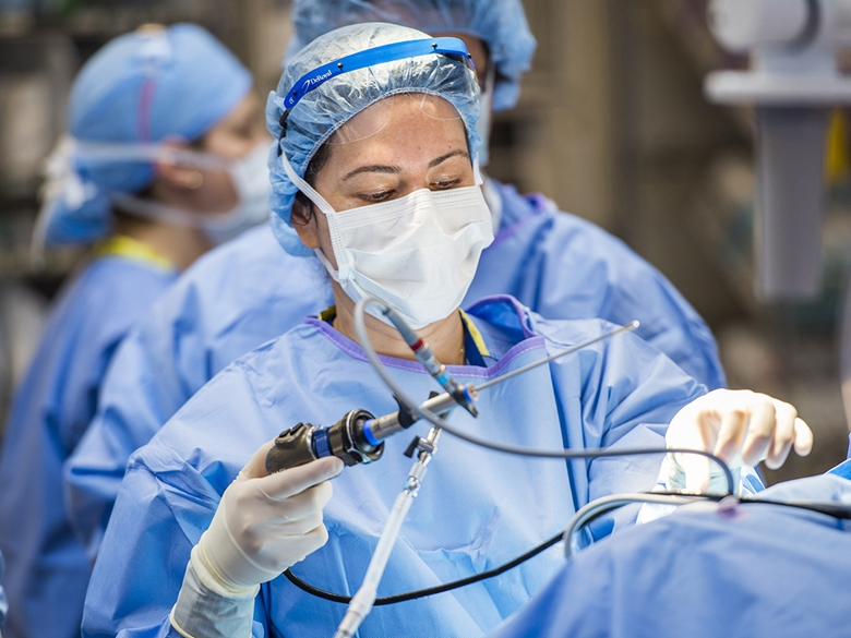 Dr. Bischoff is in the operating room, holding a surgical tool and doing surgery.