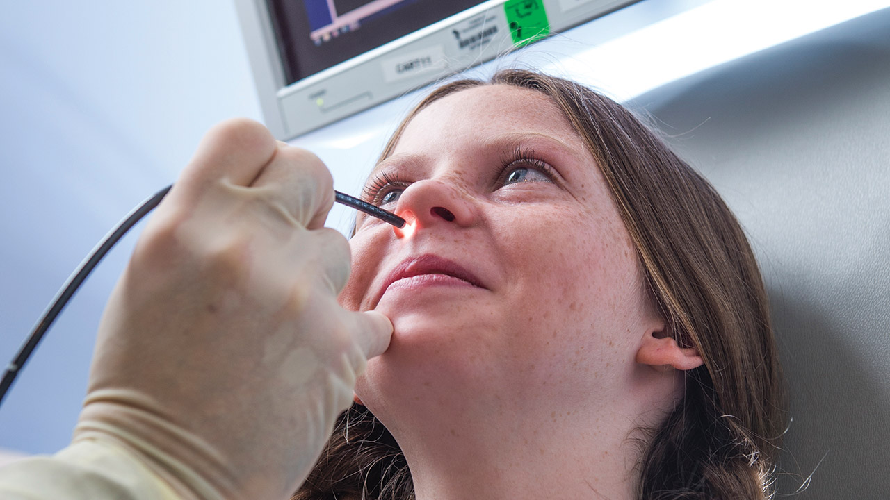 A doctor performs a nasal endoscopy procedure on a girl.