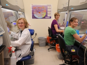 Three women sit at desks in the research lab.