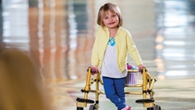Lexi, a patient at Children's Hospital Colorado, stands holding a walker.