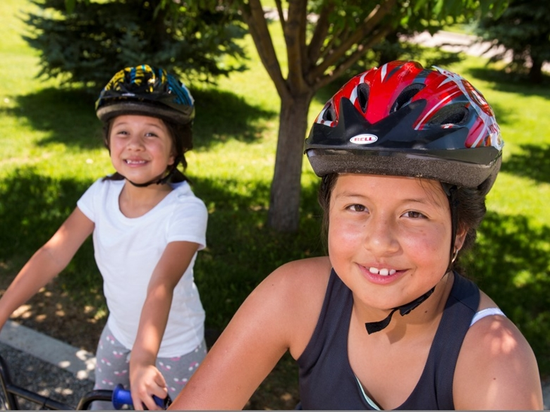 Two girls wearing helmets stand on their bikes in a park.